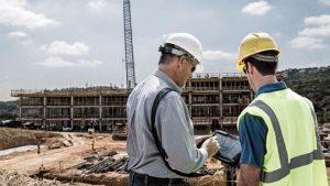 deux ouvriers consultant une tablette sur un chantier