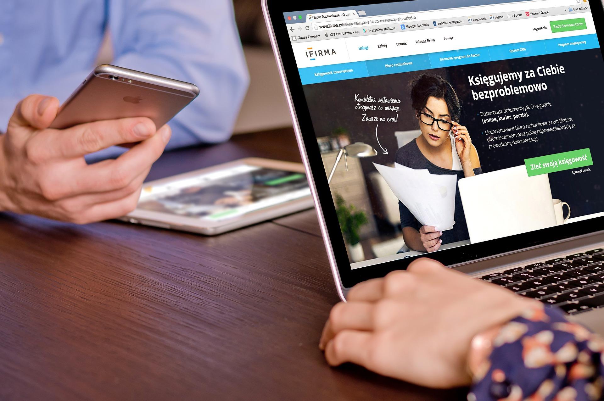 Un homme et une femme qui tiennent dans leurs mains un ordinateur portable, une tablette et un téléphone portable