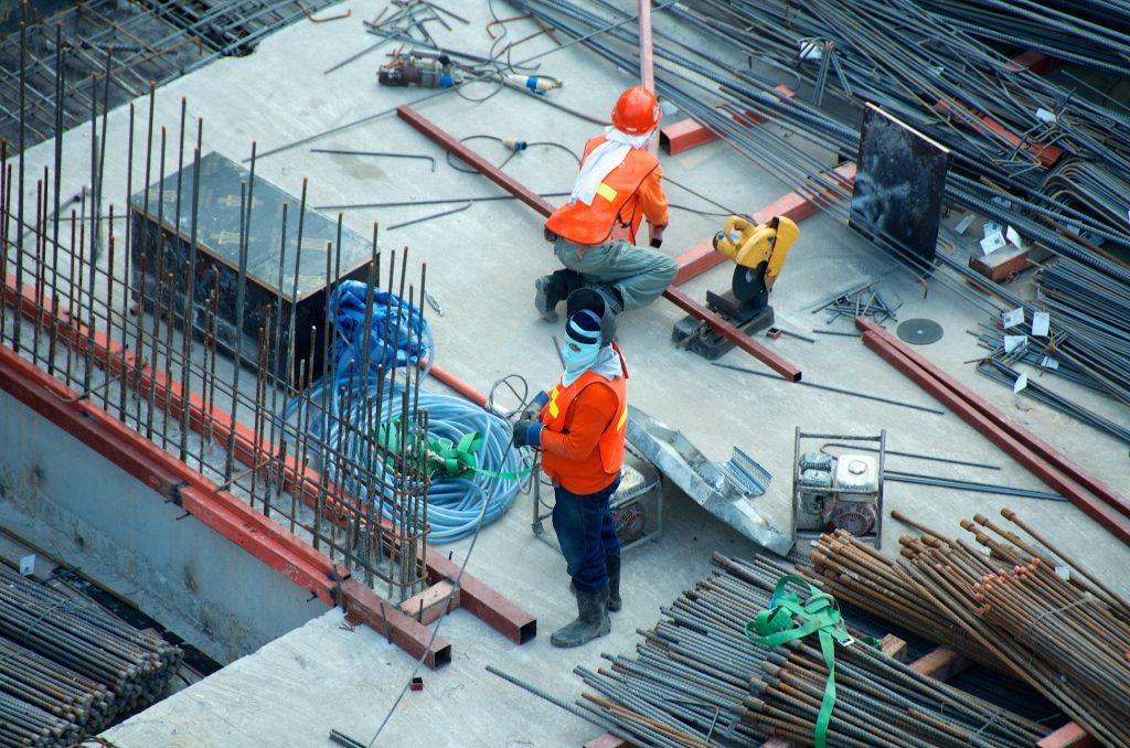 Deux ouvriers en tenue de travaux sur une surface en construction