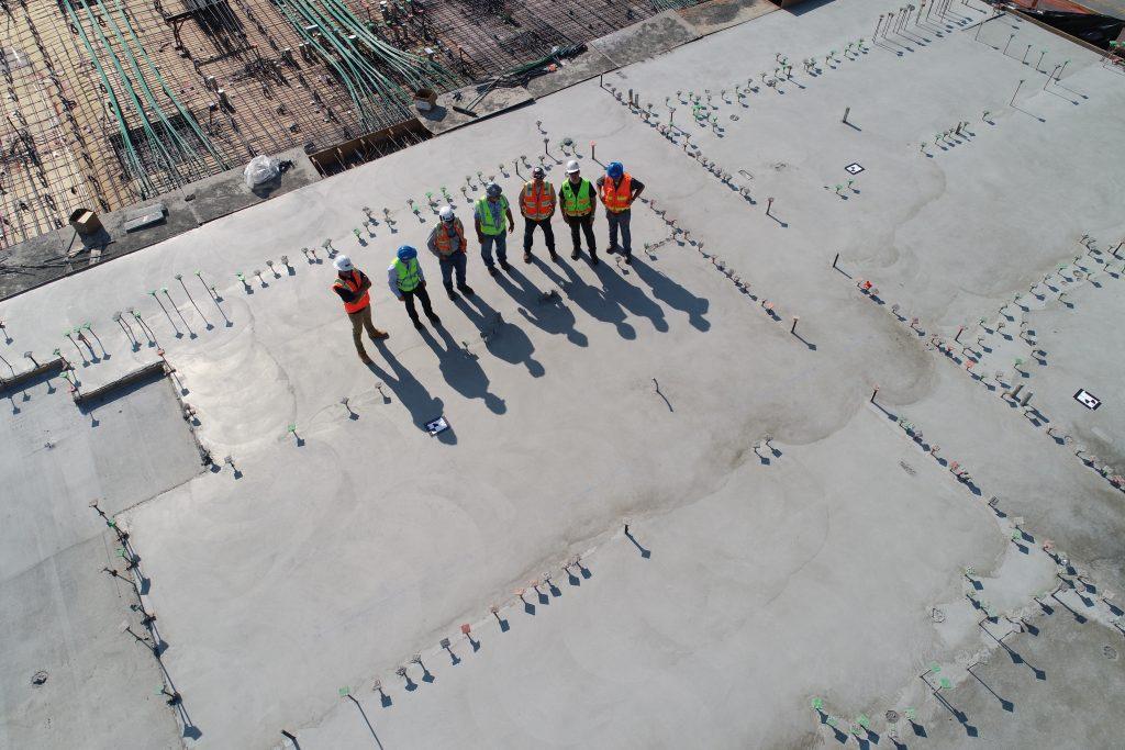 Vue aérienne d'un groupe d'ouvriers sur le toit d'un batîment en travaux