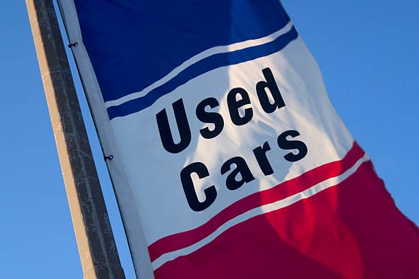 """Drapeau bleu, blanc et rouge avec l'inscription """"Used Cars"""", soit """"Voitures d'occasion"""""""