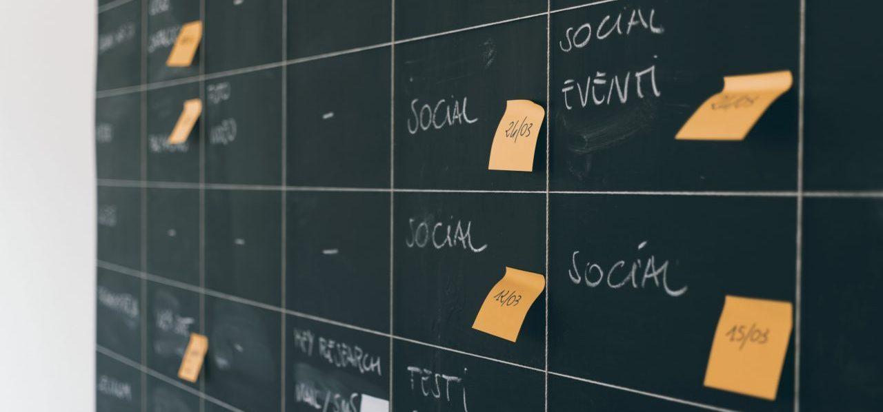 Planning salon professionnel d'une entreprise sur un tableau noir avec post-it