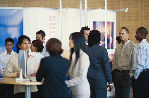 Stand entreprise avec visiteurs pendant un événement professionnel