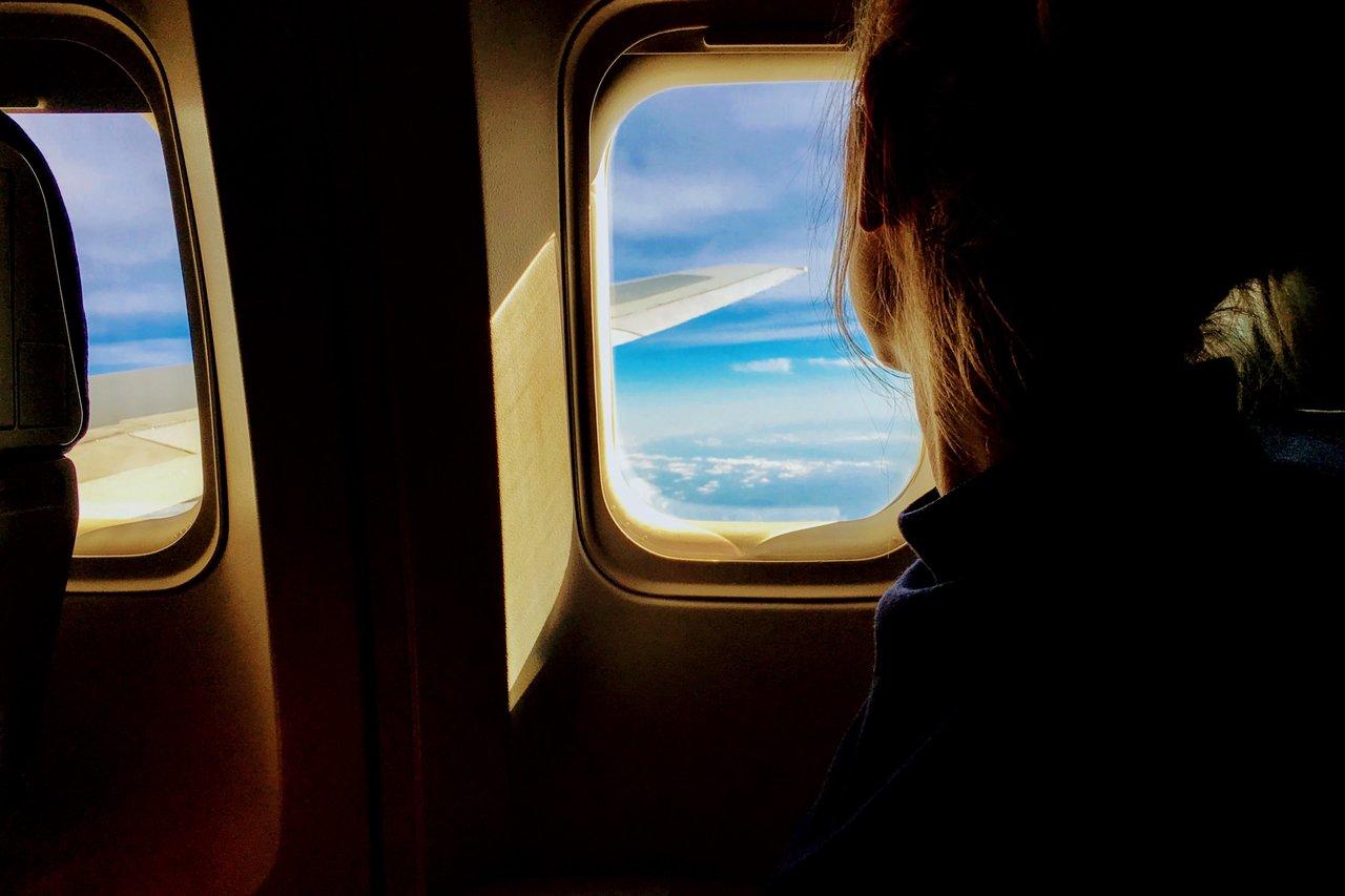 Femme qui regarde par le hublot d'un avion