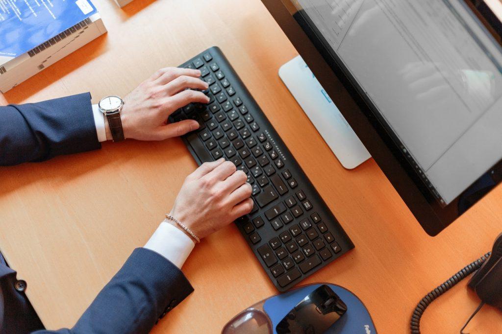 personne en costule qui tape sur un clavier d'ordinateur